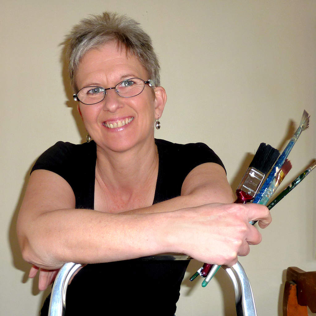 artist-Di-Fox-holding-paint-brushes-in-her-hand