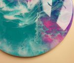 close up detail of round abstract art showing swirls and foam details in pink teal white and purple