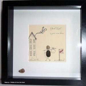 moving house pebble art for a musician man with a back pack walking towards his new house for sale sign crossed out and now says sold smoke from chimney is musical notes