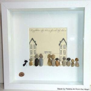 pebble picture for neighbours who are moving. Two houses a street sign eleven pebble people and one dog